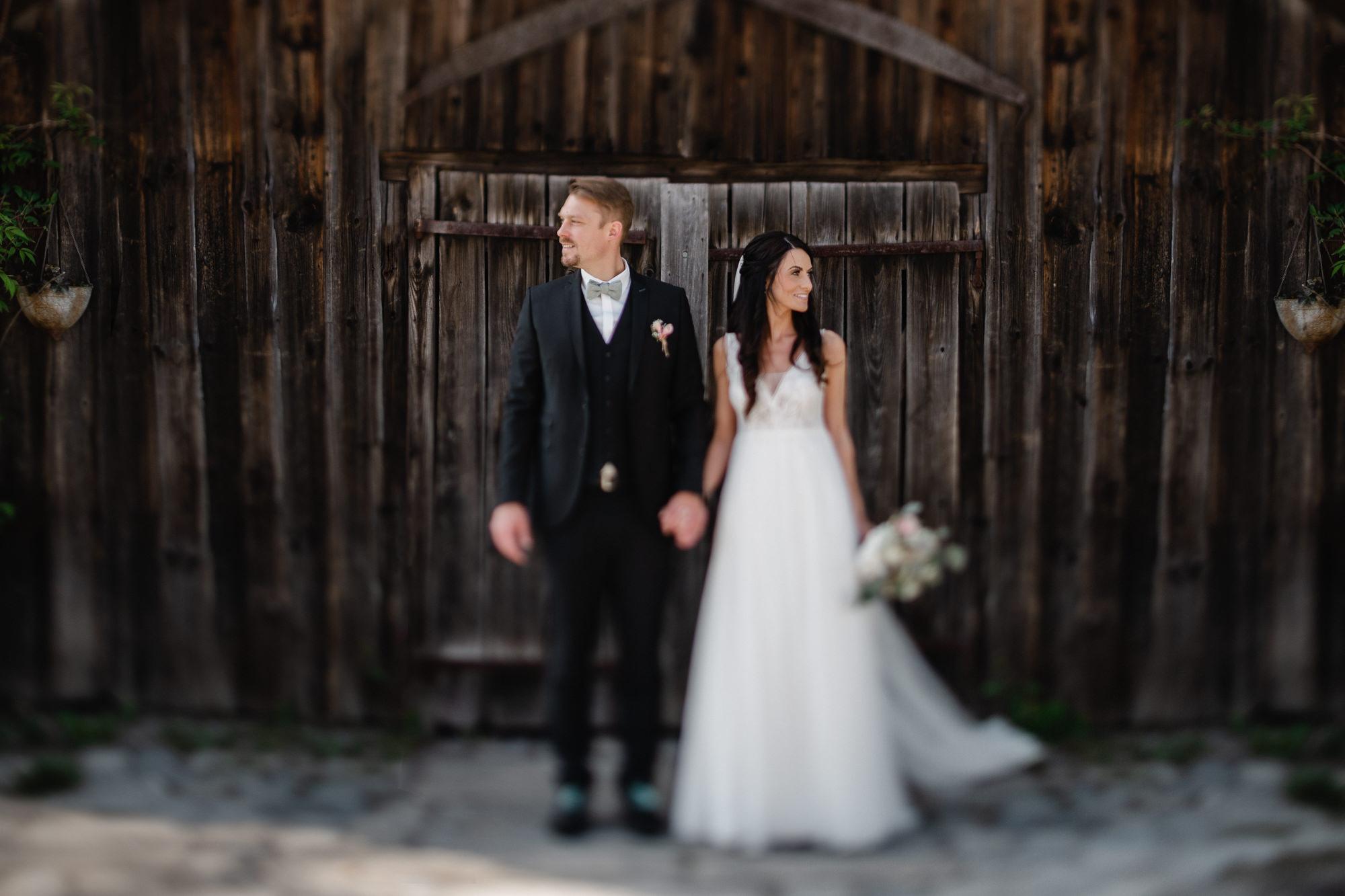 Hochzeit auf der Gutsalm Harlachberg, Paarshooting, Paar steht vor Holztür