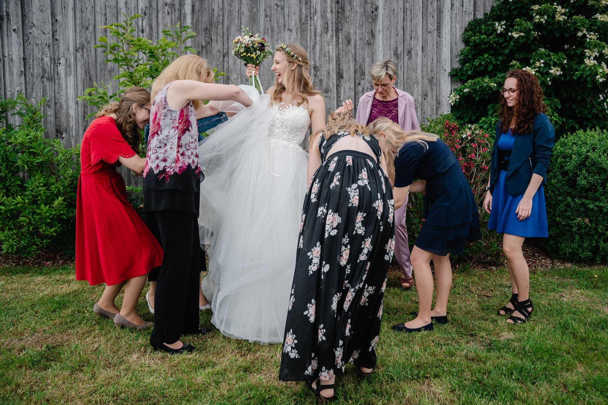 Hochzeit in Regensburg, Paarshooting, Braut wird lachend von den weiblichen Gästen fertig für das Shooting gemacht