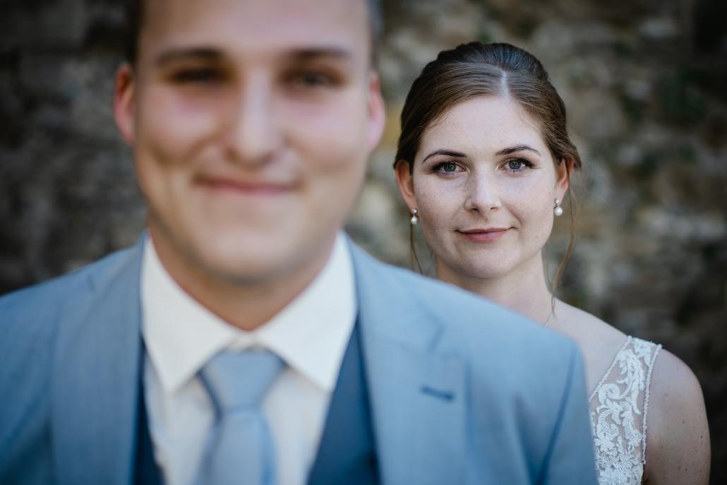 Hochzeit in Passau, Veste Oberhaus, Paarshooting, die Braut steht hinter dem Bräutigam und blickt in die Kamera