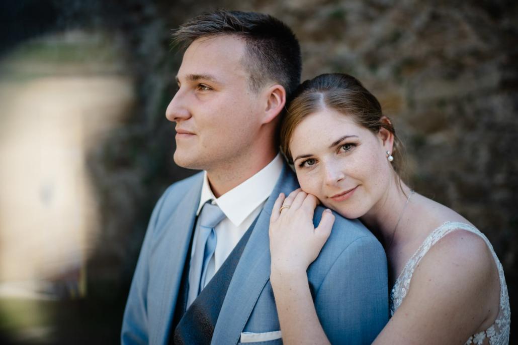 Hochzeit in Passau, Veste Oberhaus, Paarshooting, Braut schaut in die Kamera, während der Bräutigam in die Ferne blickt